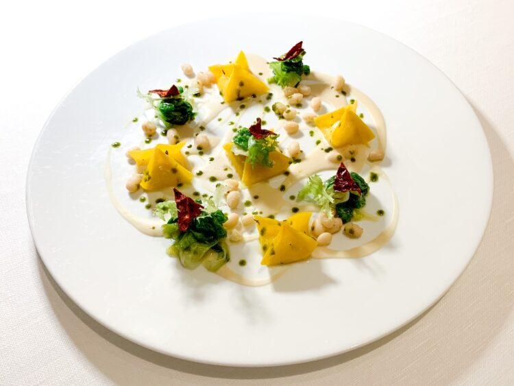 """Egg pasta stuffed with 36-month old Parmigiano Reggiano cheese, beans, endive, and """"cruschi"""" peppers"""