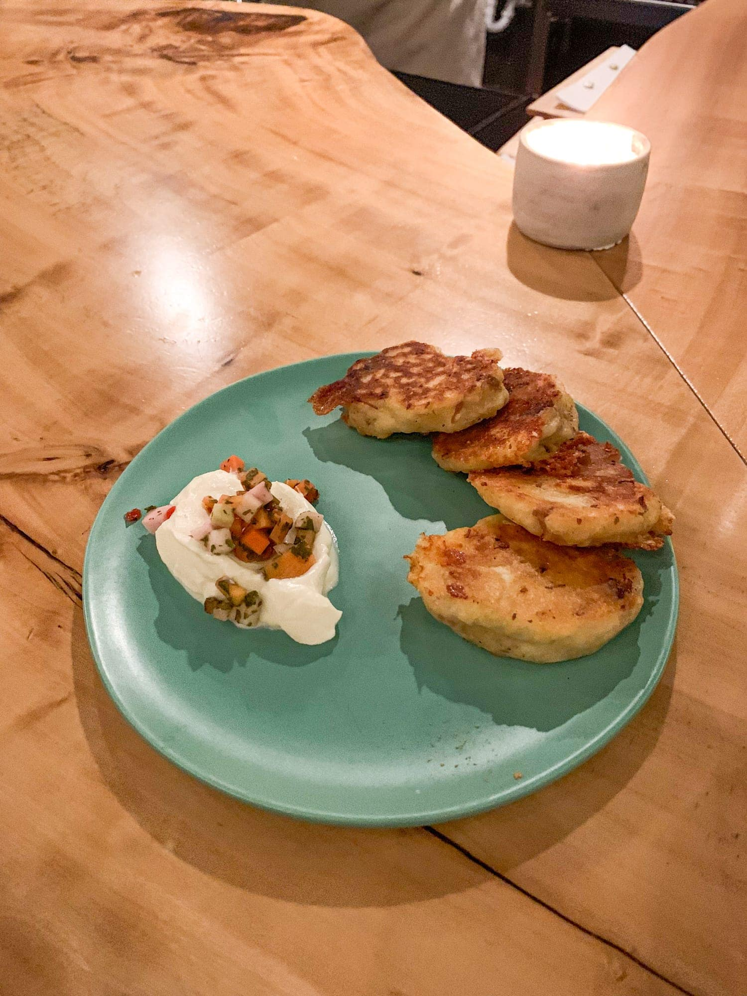 Yellow bolita Johnny Cakes with Texas Gold Cheddar, pork shoulder, and creme fraiche