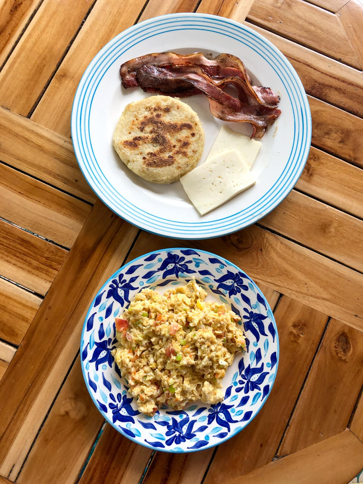 Colombian breakfast: scrambled eggs, bacon, arepa, and cheese