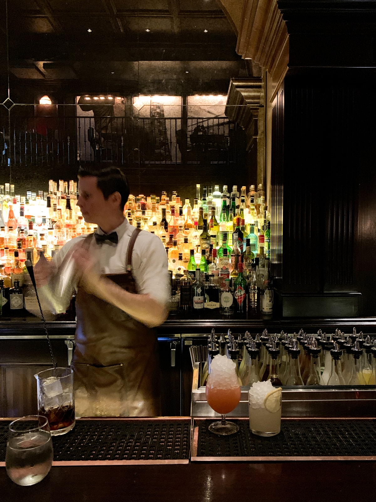Mixing drinks at Nomad Bar in NYC